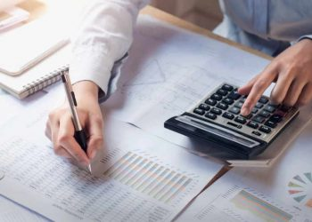 finance and accounting concept. business woman working on desk using calculator to calculate in office